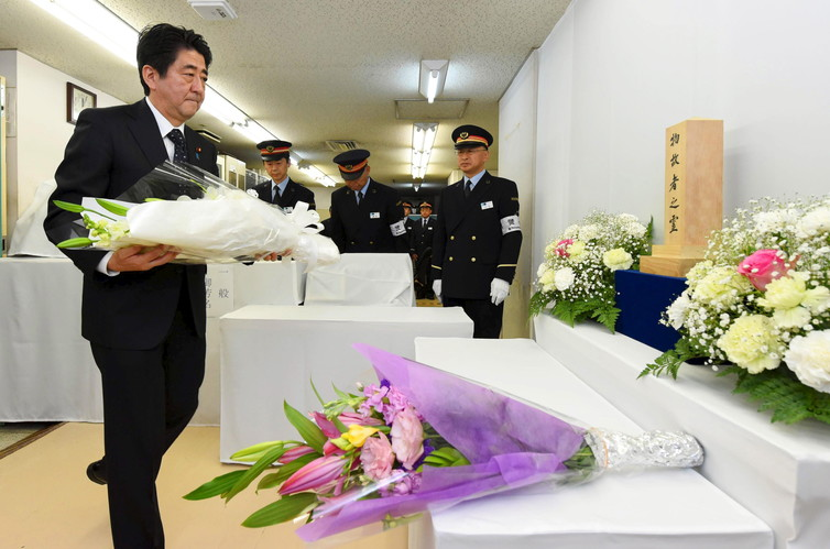 Japan's Prime Minister Shinzo Abe offers flowers to victims of the sarin poison gas attack. Credit: Reuters