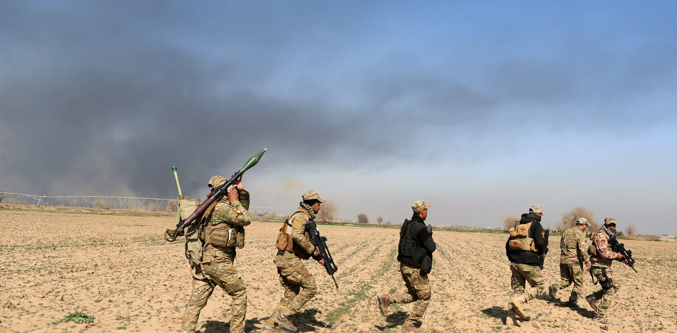 Rapid Response forces members cross farm land during a battle with ISIS's militants south west of Mosul, Iraq February 24, 2017. Credit: Reuters