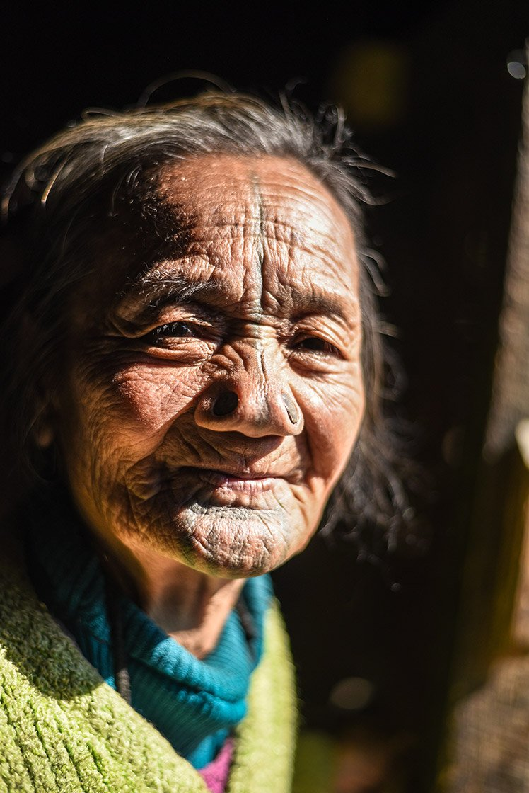 """Hibyu Era, around 90, of Hong village, with the traditional tattoo marks of the Apatani tribe on her nose, forehead and chin. Women of the Apatani tribe wear distinctive nose plugs called yapping hurlo – these are a rite of passage marking an advent into adulthood. The practice, along with their dark facial tattoos, says Narang Yamang, an Apatani community worker, originated as a deterrent – during raids by rival tribes, women were kidnapped and never seen again. The nose rings and the tattoos, says Narang, were meant """"to make us look less appealing (to the raiders)."""" These body alterations are a fading ritual that has not been practiced since 1970."""