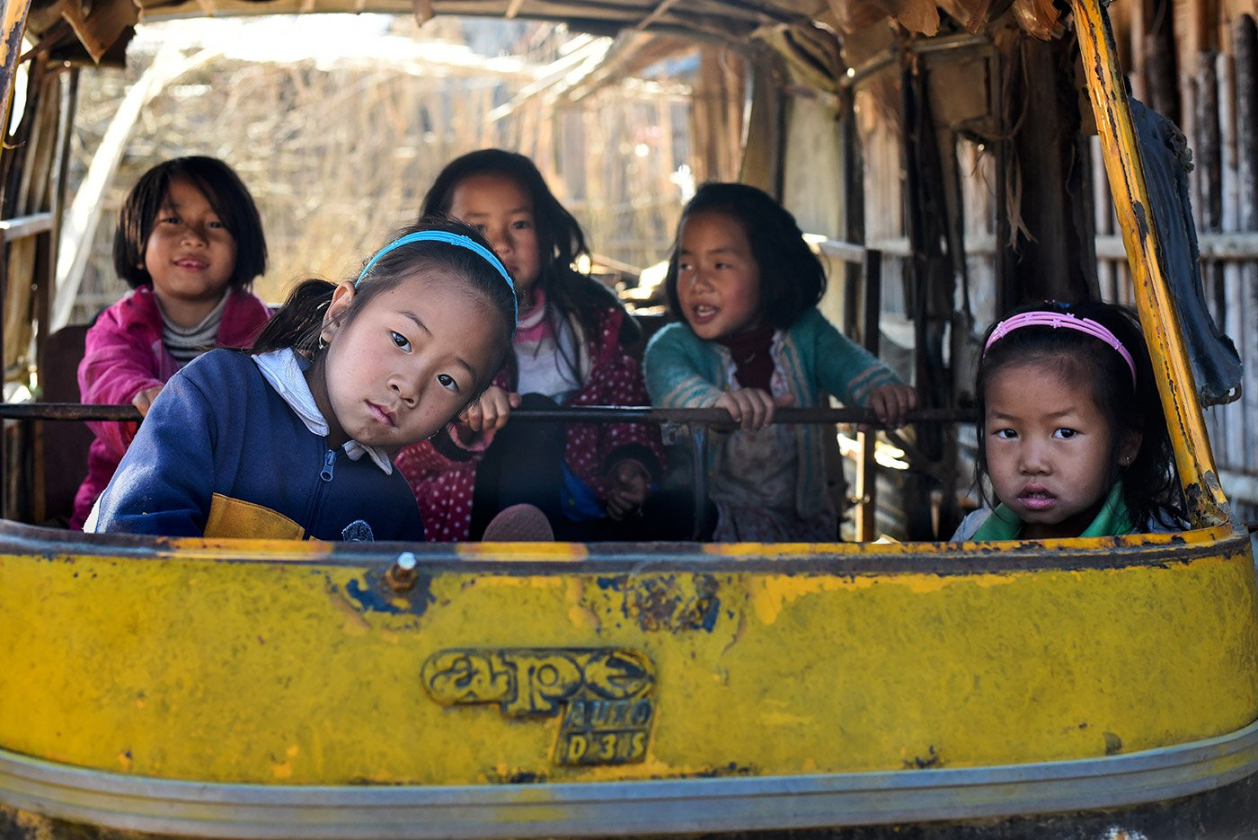 Takelimu, a nine year old old Apatani girl (in blue jacket) playing inside a broken auto in Hong village.
