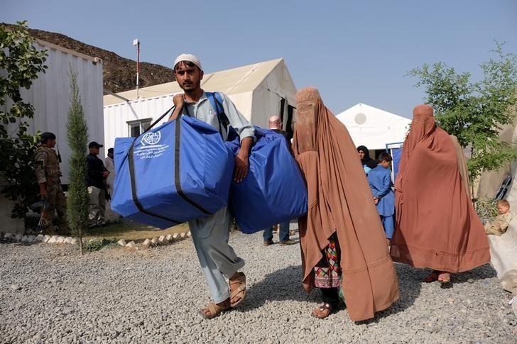 An Afghan family, who were living as refugees in Pakistan, carries bundles of supplies at a humanitarian aid station in Torkham, Afghanistan, October 22, 2016. Credit: Reuters