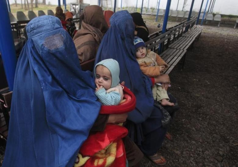 Afghan refugee women sit with their babies as they wait with others to be repatriated to Afghanistan, at the United Nations High Commissioner for Refugees (UNHCR) office on the outskirts of Peshawar, February 2, 2015. Credit: Reuters