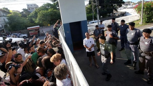 A military police officer (R) talks with relatives of police officers who are blocking the main entrance of police headquarters, during a police strike over wages, in Vitoria, Espirito Santo, Brazil February 11, 2017. Credit: Reuters
