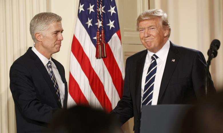 US President Donald Trump shakes hands with Neil Gorsuch (L) after nominating him to be an associate justice of the US Supreme Court at the White House in Washington, DC, US, January 31, 2017. Credit: Reuters/Kevin Lamarque