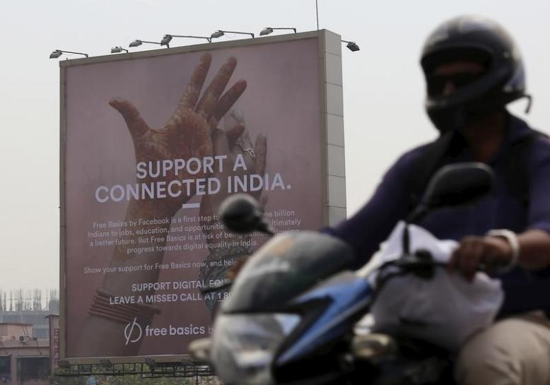 A motorist rides past a billboard displaying Facebook's Free Basics initiative in Mumbai. Credit: Reuters