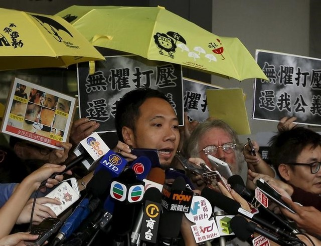 Pro-democracy Protester Ken Tsang Kin-chiu, surrounded by supporters holding yellow umbrellas, symbols of the Occupy Central movement, and reporters, speaks outside a court in Hong Kong, China October 19, 2015. Credit: Reuters
