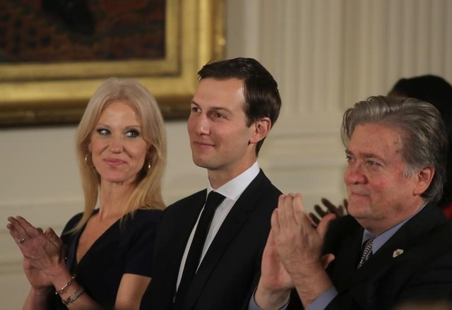 Senior staff at the White House Kellyanne Conway, Jared Kushner and Steve Bannon (L-R) applaud before being sworn in by Vice President Mike Pence in Washington, DC January 22, 2017.  Credit: Reuters