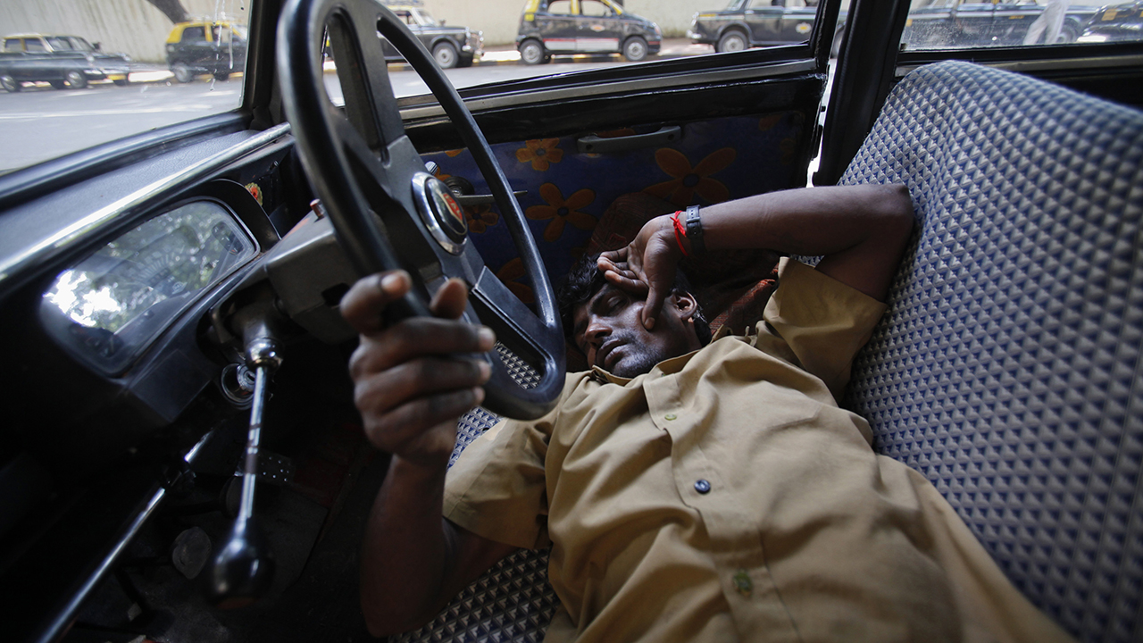 A taxi driver takes an afternoon nap with his hand on the steering wheel of his Premier Padmini taxi in Mumbai October 2, 2012. The Premier Padmini was manufactured in India by Premier Automobiles from 1964 to 2000 and is based on the design of Fiat's 1100-series cars from the 1960s. The vehicle quickly became the iconic workhorse in Mumbai's fleet of black and yellow taxis until economic liberalisation in the 1990s allowed different makes and models to be produced in India. With a government order banning taxis over 25 years old, the number of Premier Padmini taxis has begun to dwindle and, in a few years, they will be gone from Mumbai's streets altogether. Local media estimates put Mumbai's current taxi fleet at about 51,000 vehicles, of which it is estimated that about 8,000 vehicles are over 25 years old. Picture taken October 2, 2012.   REUTERS/Vivek Prakash (INDIA - Tags: TRANSPORT SOCIETY)  ATTENTION EDITORS: PICTURE 18 OF 23 FOR PACKAGE 'FAREWELL - OLD LADY OF MUMBAI' SEARCH 'PADMINI' FOR ALL IMAGES - RTR396X2