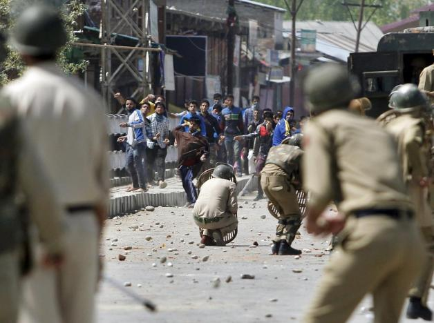 Kashmiri protesters throw stones towards Indian policemen during a daylong protest strike in Narbal, north of Srinagar April 18, 2015. Credit: Danish Ismail/Reuters/Files
