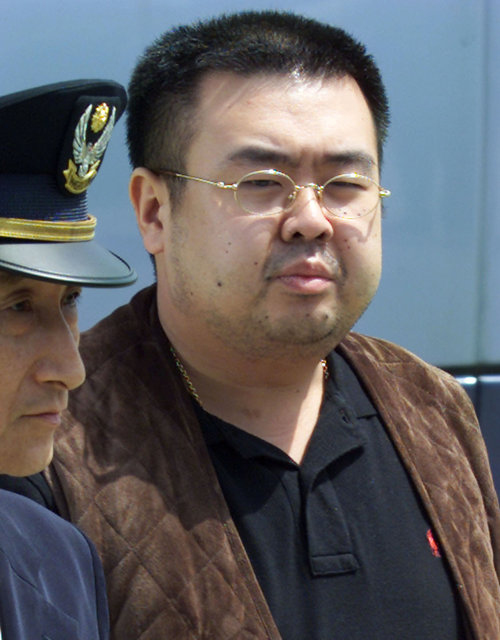 A man (R) believed to be North Korean heir-apparent Kim Jong-nam is escorted by police as he boards a plane upon his deportation from Japan at Tokyo's Narita international airport May 4, 2001. Credit: Reuters
