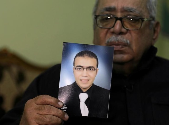 Reda Abdullah al-Hamamy, the father of Abdullah Reda al-Hamamy who is suspected of attacking a soldier in Paris'sLouvre museum, holds a picture of his son during an interview with Reuters in Daqahliya, Egypt, February 4, 2017. Credit: Reuters