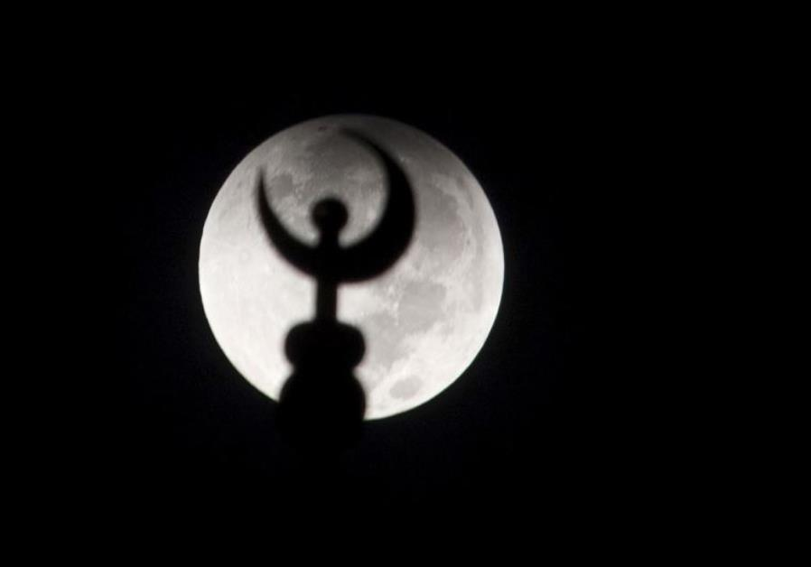 "A minaret of a mosque is silhouetted against the moon at the start of a total ""supermoon"" lunar eclipse. Credit: Reuters"