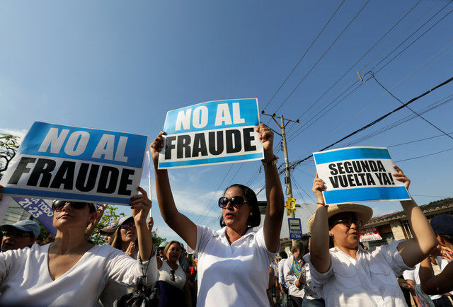 """People hold signs reading """"No to fraud"""" and """"(Election) Run-off now"""" as they protest near the electoral council in Guayaquil, Ecuador February 20, 2017. Credit: Reuters"""