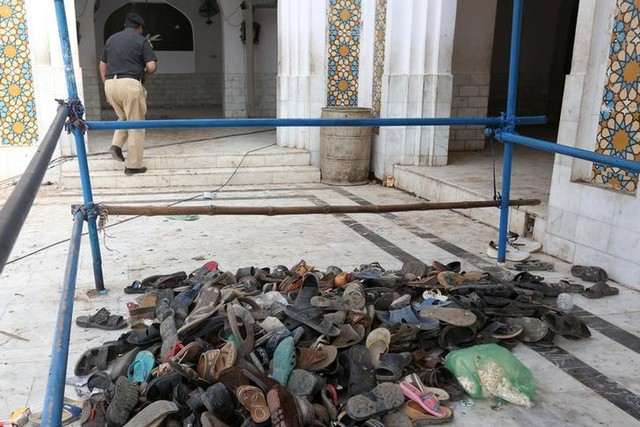 A policeman walks past a pile of shoes left by devotees after Thursday's suicide blast at the tomb of Sufi saint Syed Usman Marwandi, also known as the Lal Shahbaz Qalandar shrine, in Sehwan Sharif, Pakistan's southern Sindh province, February 17, 2017. Credit: Reuters