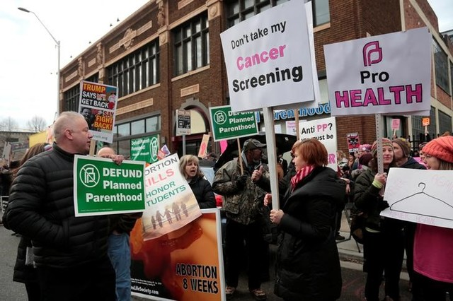 Supporters of Planned Parenthood (R) rally next to anti-abortion activists outside a Planned Parenthood clinic in Detroit, Michigan, US, February 11, 2017. Credit: Reuters