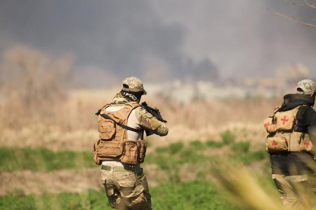 Rapid Response forces members cross farm land during a battle with ISIS's militants south west Mosul, Iraq February 24, 2017. Credit: Reuters