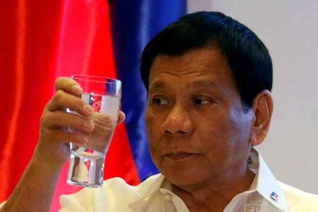 Philippine President Rodrigo Duterte raises a glass of water as he proposed a toast during the Asian Development Bank 50th anniversary in Mandaluyong, Metro Manila, Philippines February 21, 2017. Credit: Reuters