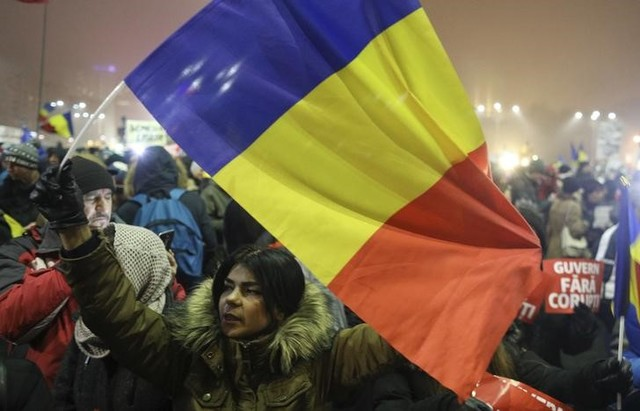 A woman waves a Romanian flag during a protest of thousands against their government in Bucharest, Romania, February 6, 2017. Credit: Reuters