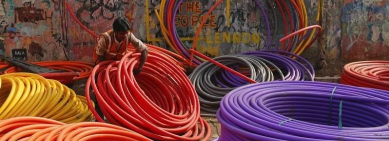 A labourer works amid rolls of underground telephone cable pipes on the side of a road in Mumbai January 9, 2014. Credit: Reuters/Danish Siddiqui/Files