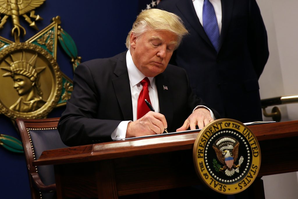 US President Donald Trump signs an executive order to impose tighter vetting of travellers entering the United States on January 27, 2017. Credit: Reuters