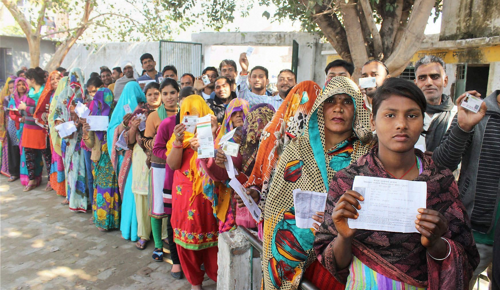 Voters wait in queue to cast their votes during the first phase of UP Assembly polls in Meerut district on Saturday. Credit: PTI