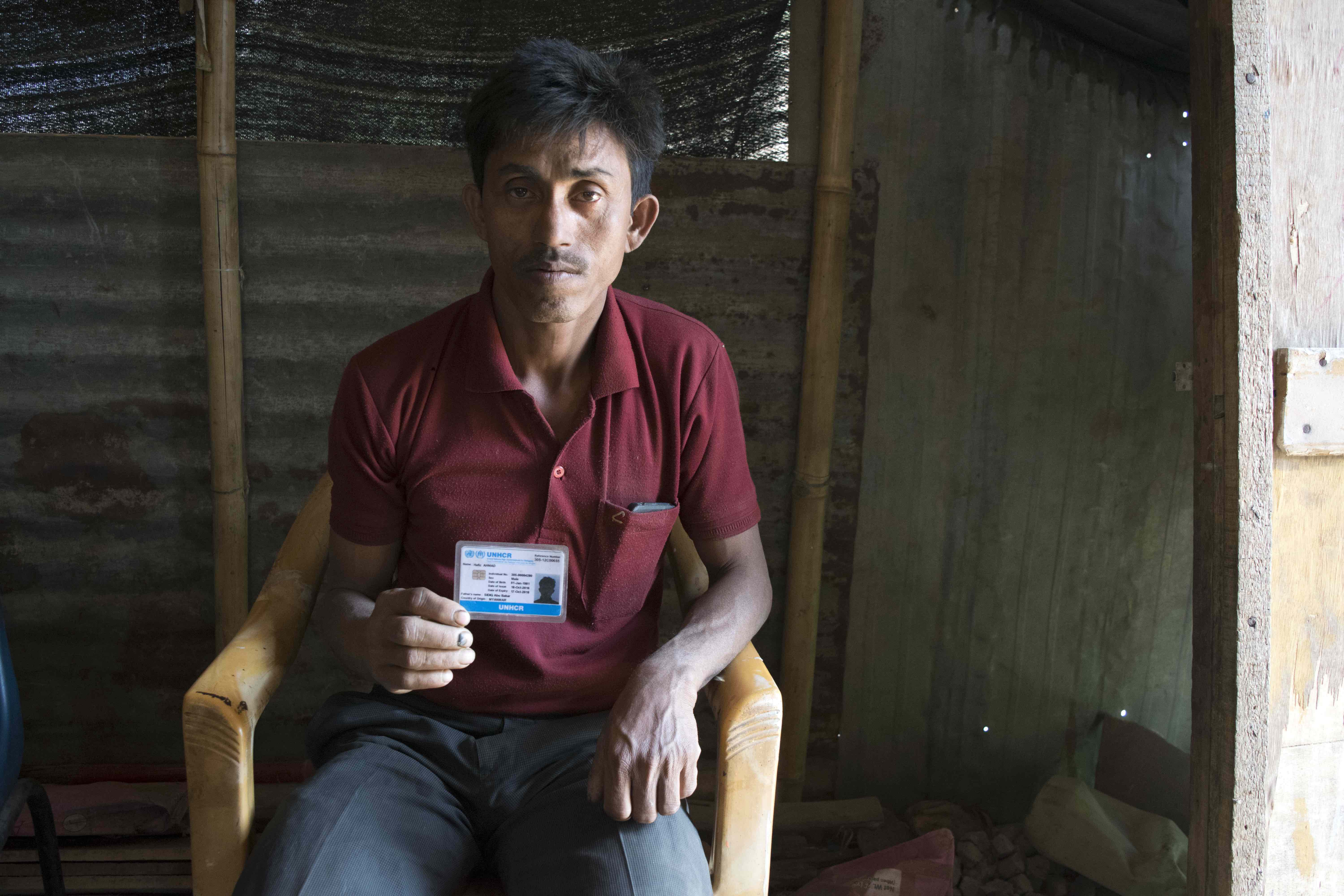 Hafij Ahmad, 35, holds his UNHCR refugee card. The identification card prevents deportation and allows refugees and aslyum-seekers to apply for a long-term visa of one-year duration, which can be renewed each year. The long-term visa potentially helps in securing employment and higher education. Credit: Meagan Clark