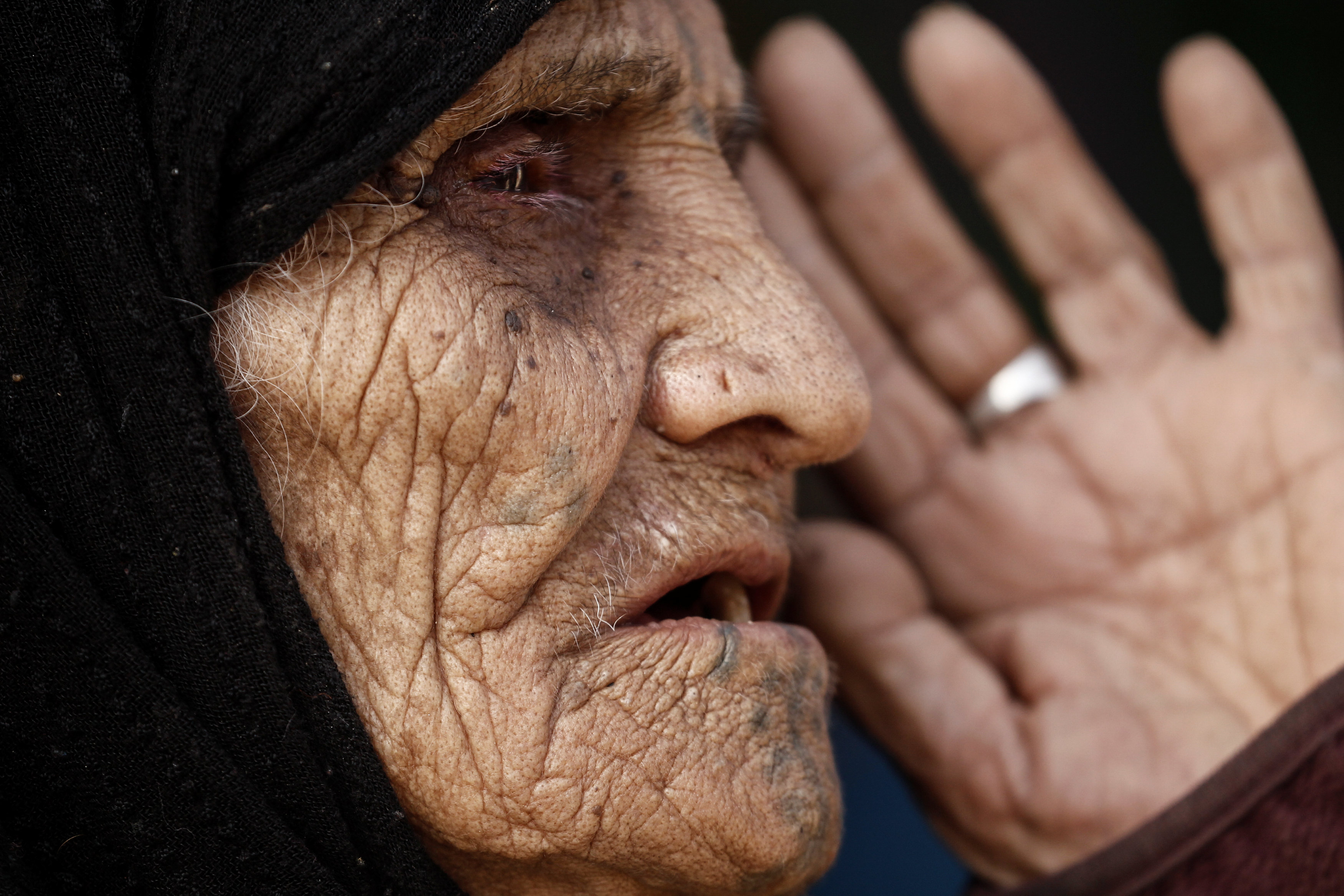 Khatla Ali Abdullah, 90, who recently fled her house in Al Mamoun district speaks with a Reuters journalist as she sits at her tent in Hammam al Alil camp, while Iraqi forces battle with Islamic State militants, in western Mosul, Iraq March 1, 2017. Credit: Zohra Bensemra/Reuters