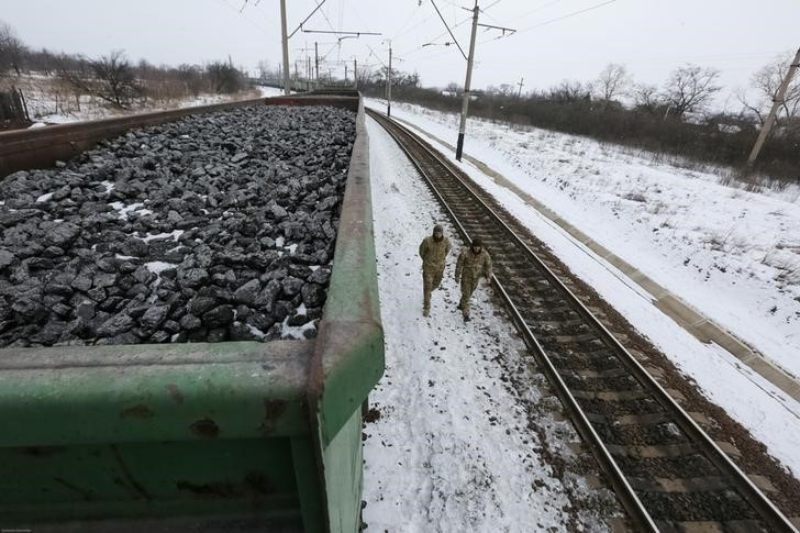 Activists walk along carriages loaded with coal from the occupied territories which they blocked at Kryvyi Torets station in the village of Shcherbivka in Donetsk region, Ukraine, February 14, 2017. Credit: Konstantin Chernichkin/Reuters