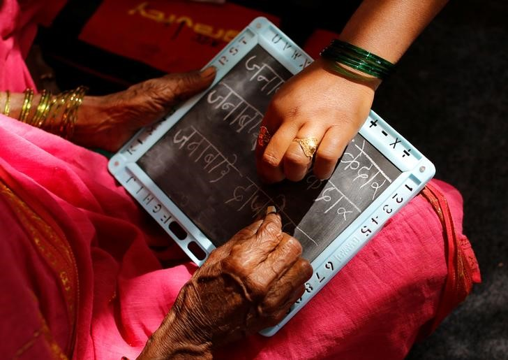 Sheetal Prakash More (R), a 30-year-old teacher, helps Janabai Kedar, 74, as she writes on a slate at Aajibaichi Shaala (Grandmothers' School) in Fangane village, India, February 15, 2017. Credit: Danish Siddiqui/Reuters