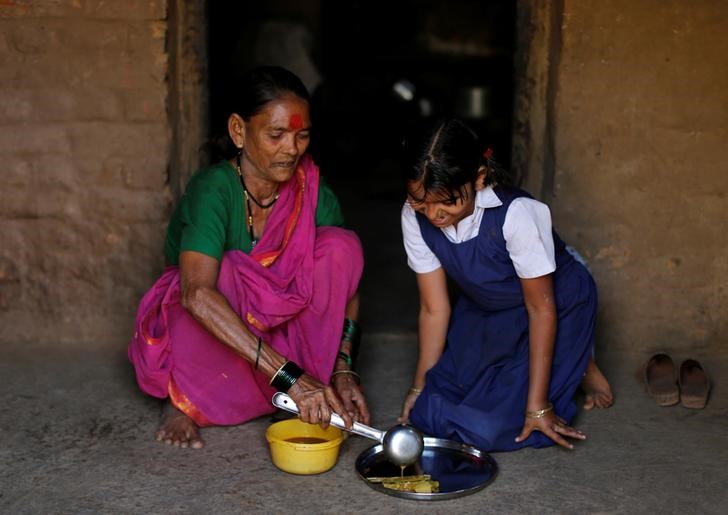 Drupada Pandurangkedar, 70, who studies at Aajibaichi Shaala (Grandmothers' School), serves her granddaughter Namita Thackrey lunch inside their house in Fangane village, India, February 15, 2017. Credit: Danish Siddiqui