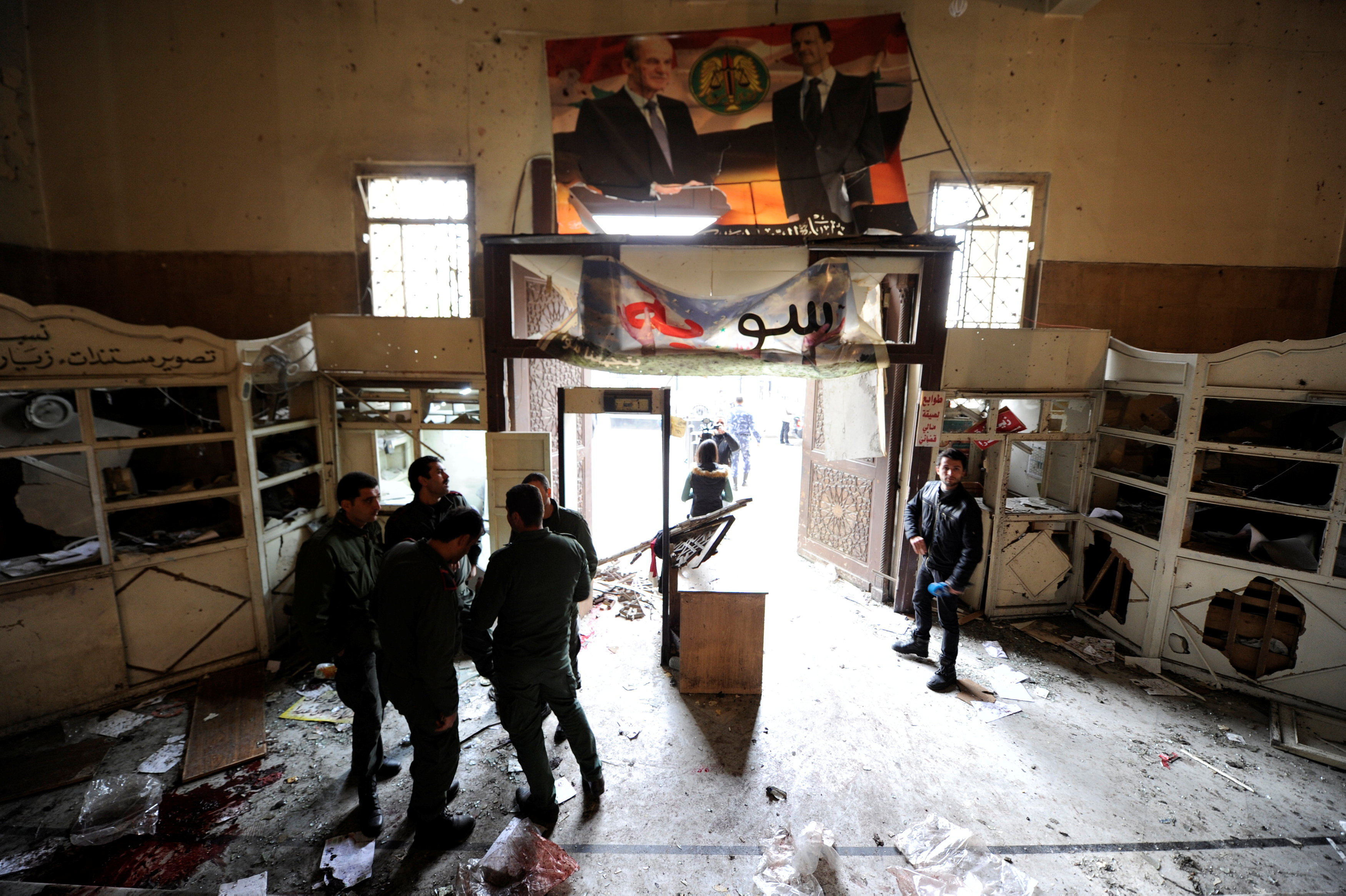Security personnel stand near a damaged entrance after a suicide blast at the Palace of Justice in Damascus, Syria March 15, 2017. Credit: Omar Sanadiki/Reuters