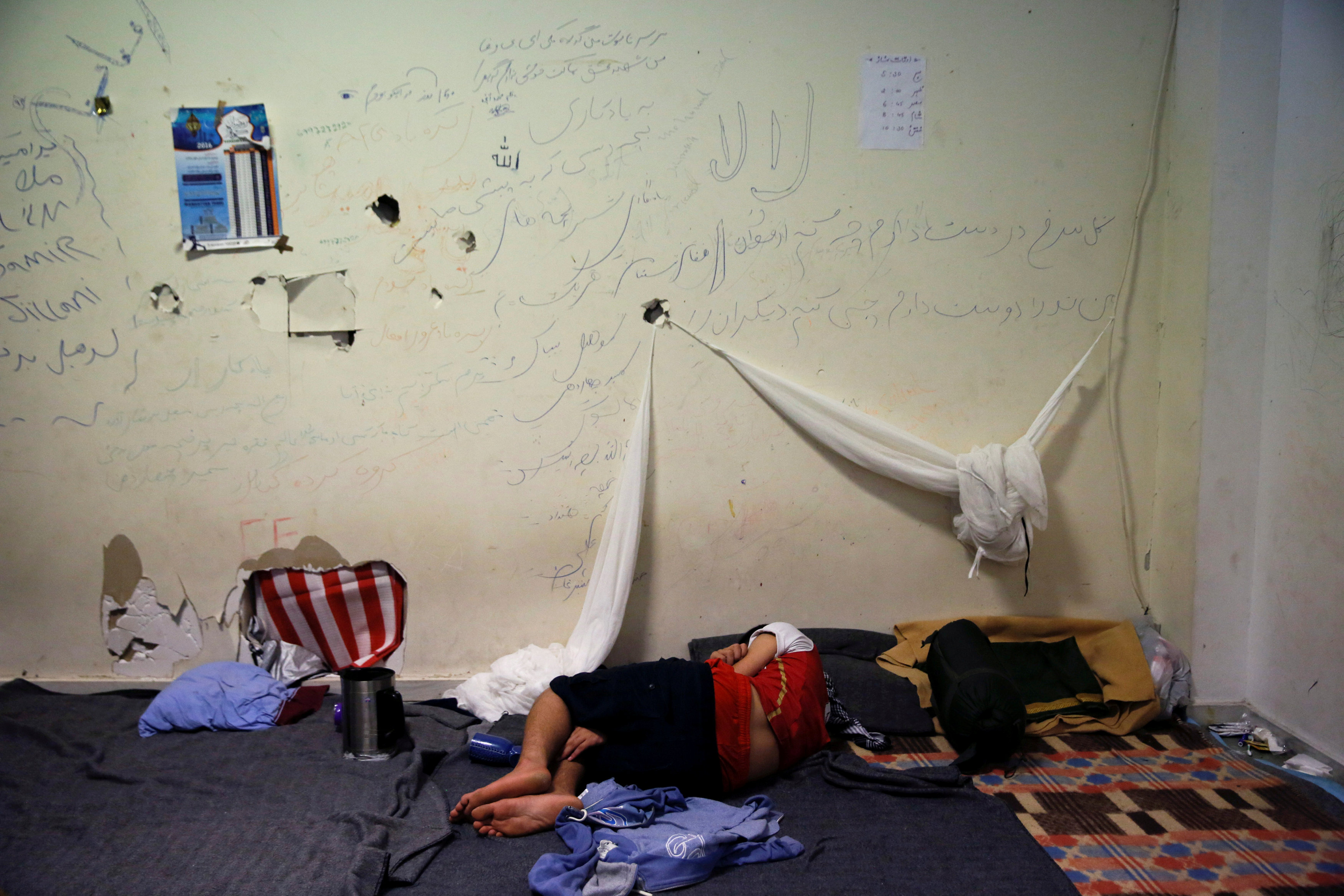 A boy sleeps inside the disused Hellenikon airport where refugees and migrants are temporarily housed in Athens, Greece July 13, 2016. Credit: Alkis Konstantinidis/Files