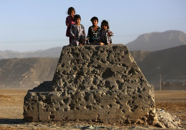 Afghan children sit on a bullet-riddled concrete block in Kabul October 21, 2013. Credit: Mohammad Ismail/Reuters/Files