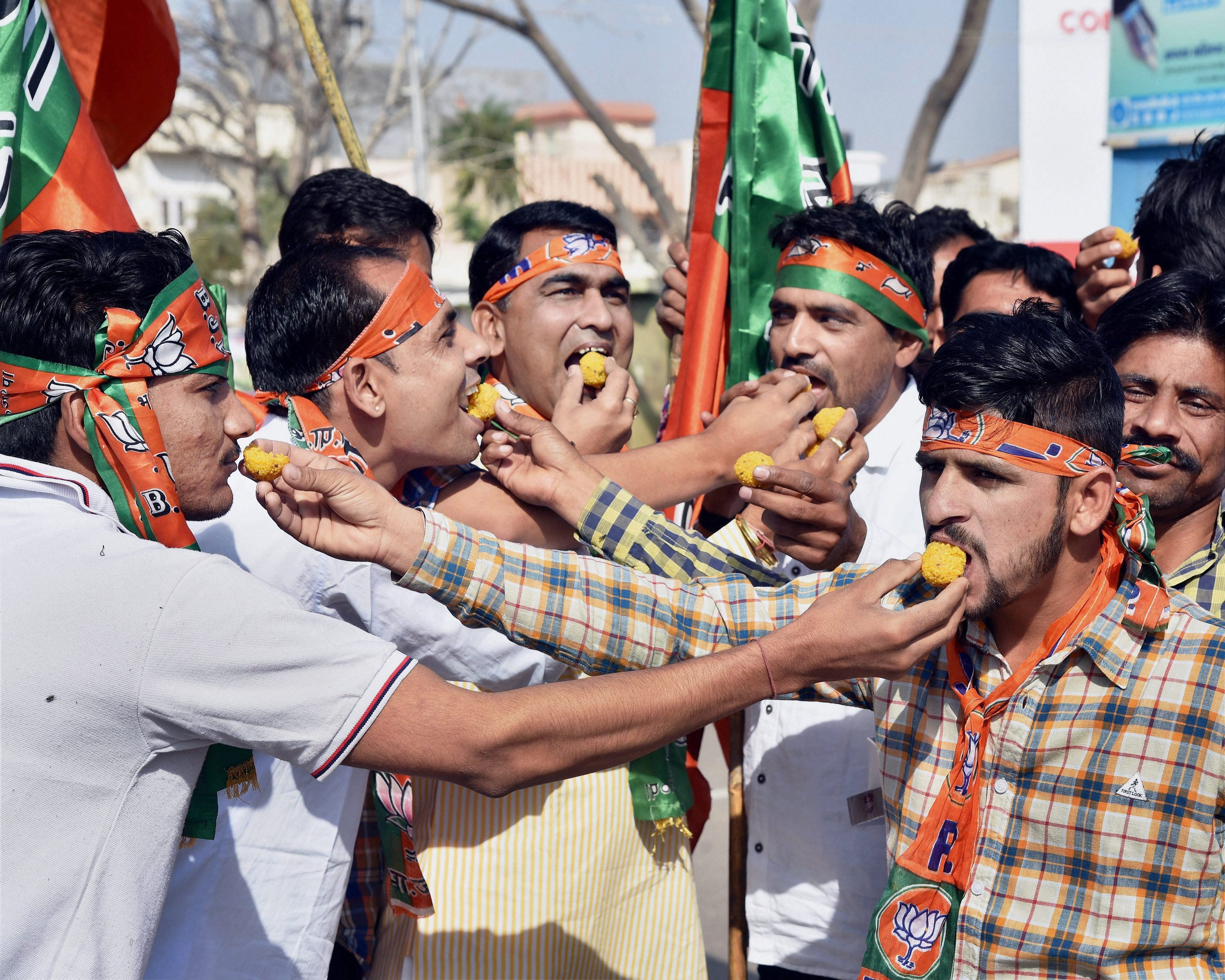Bikaner: BJP supporters celebrate as early trends show the party's thumping win in the UP Election Results assembly polls, in Bikaner on Saturday. PTI Photo (PTI3_11_2017_000025B)