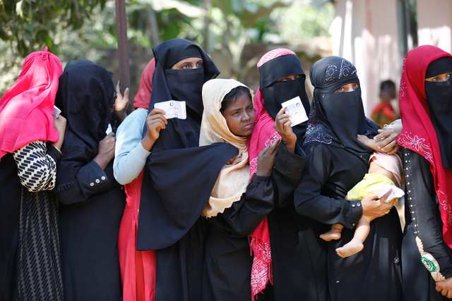 Rohingya women wait in a queue with vouchers to collect relief distributed by the Bangladesh Red Crescent Society at Kutupalang Unregistered Refugee Camp in Cox's Bazar, Bangladesh. Credit: Reuters/Mohammad Ponir Hossain
