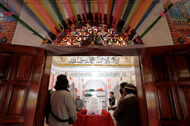 People say a prayer over the grave of Mumtaz Qadri at the shrine built over his grave outside Islamabad, Pakistan February 27,  2017. Credit: Caren Firouz/Reuters