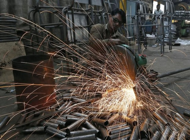 A worker cuts a metal pipe inside a steel furniture production factory in Ahmedabad February 2, 2015. Credit: Reuters/Amit Dave/Files