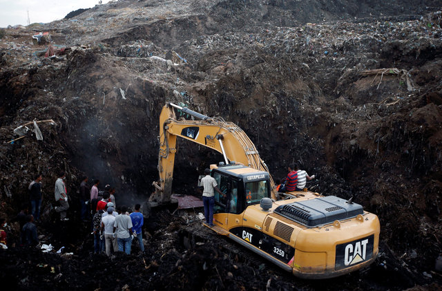 Rescue workers watch as excavators dig into a pile of garbage in search of missing people following a landslide when a mound of trash collapsed on an informal settlement at the Koshe garbage dump in Ethiopia's capital Addis Ababa, March 13, 2017. Credit: Reuters/Tiksa Negeri