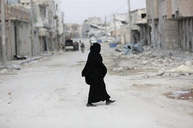 A woman walks through a damaged neighbourhood in the northern Syrian town of al-Bab, Syria March 4, 2017. Credit: Khalil Ashawi/Reuters