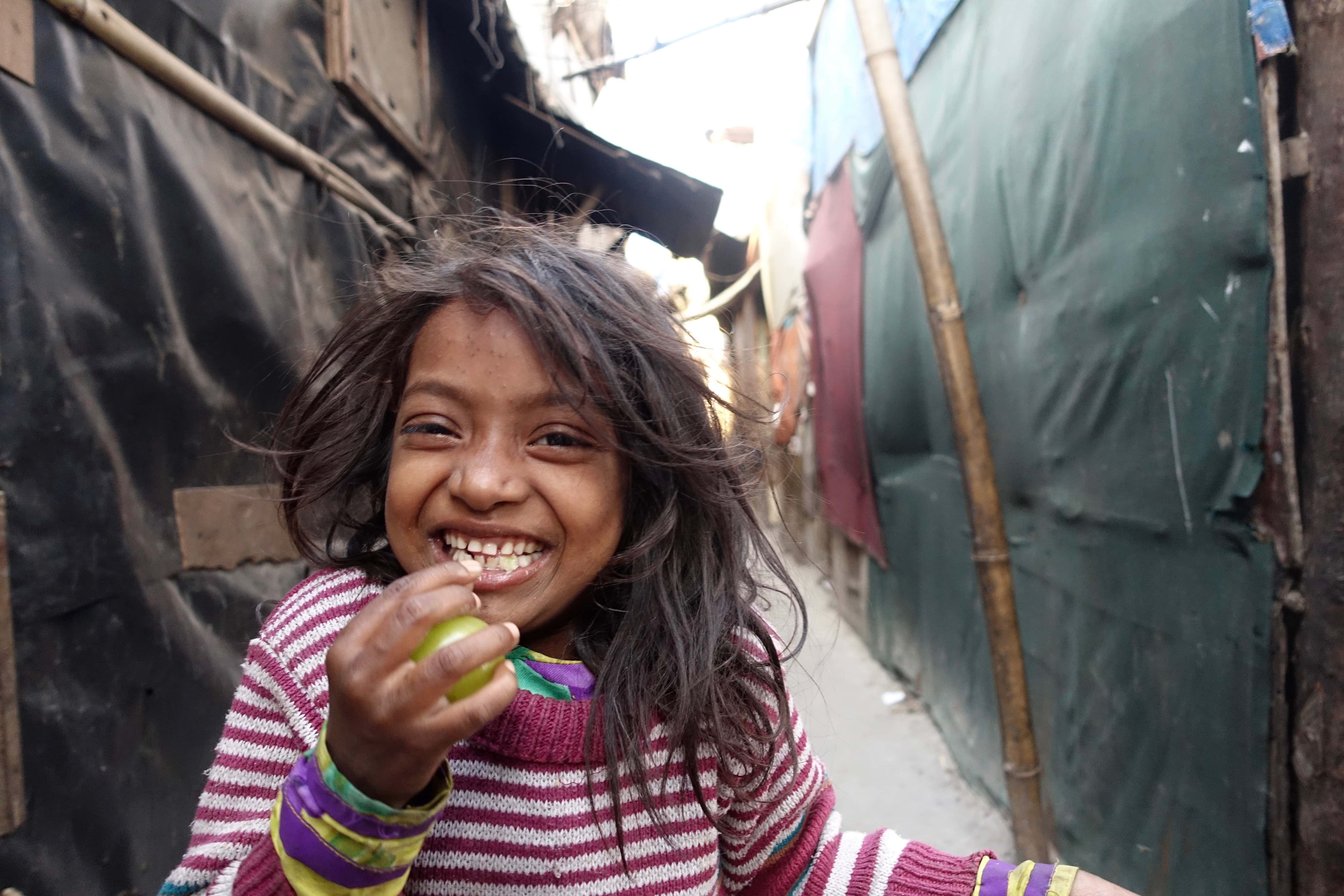A young girl smiles at the camera. The space between the huts in Kalindi Kunj is narrow and a popular place for the kids to play chase. Credit: Bill Drexel.