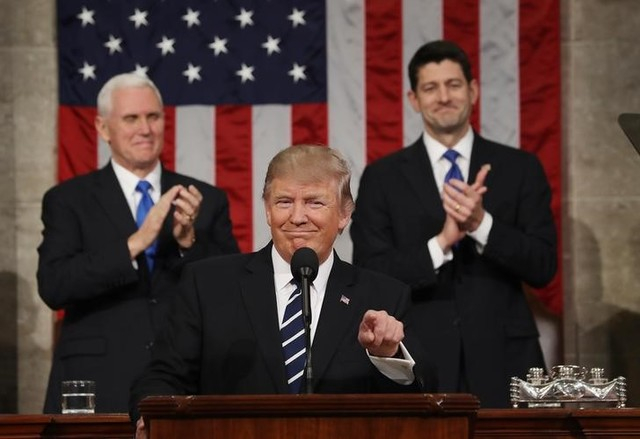US vice president Mike Pence (L) and Speaker of the House Paul Ryan (R) applaud as US President Donald J. Trump (C) arrives to deliver his first address to a joint session of Congress from the floor of the House of Representatives in Washington, DC, US, 28 February 2017. Credit: Reuters