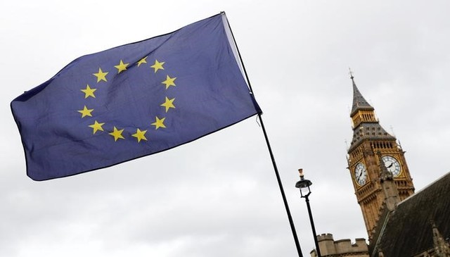 A EU flag is waved in front of Big Ben outside Parliament after Britain's Prime Minister Theresa May triggered the process by which the UK will leave the EU in London, March 28, 2017. Credit: Reuters