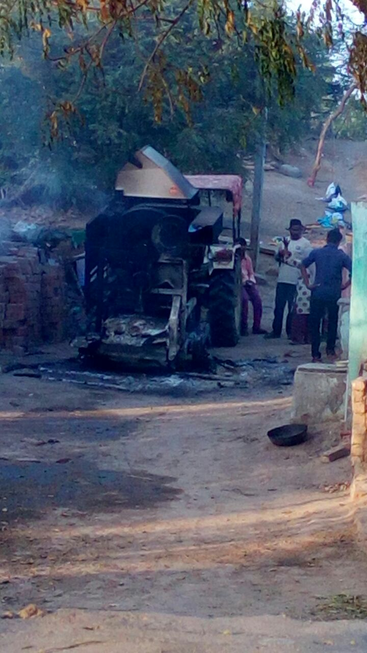 A woman who has also lost her house shows her burnt tractor to the police and recounts the madness that struck the village. Credit: Damayantee Dhar