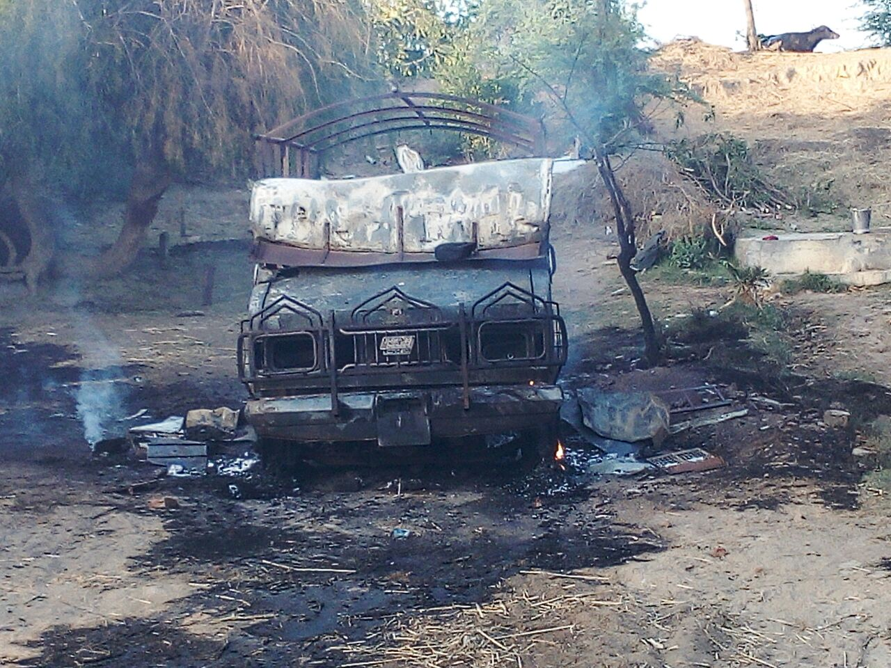 What's left of the village: burnt houses, vehicles and looted or destroyed food grain. Credit: Damayantee Dhar