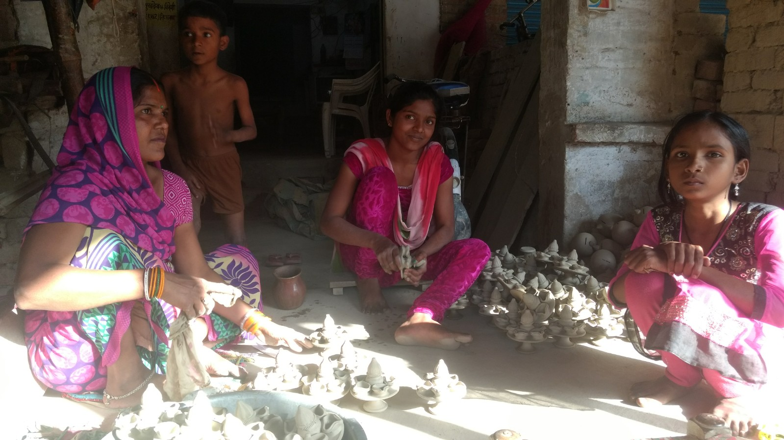 Prema Devi with her daughters making diyas in Nizamabad. Credit: Titash Sen