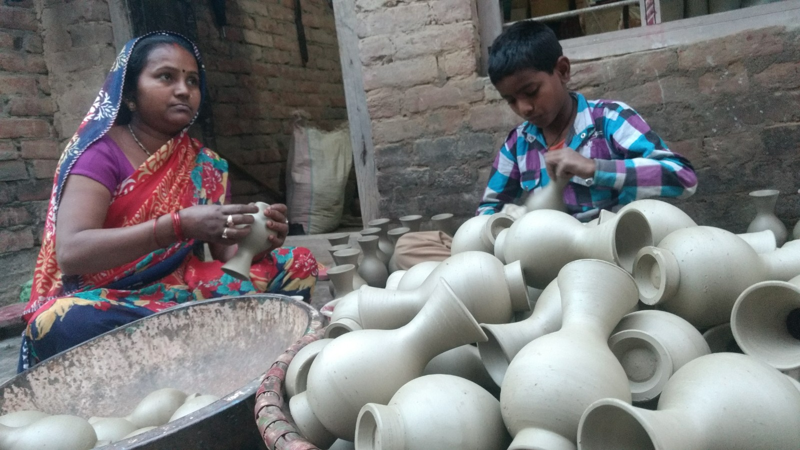 A woman and her son polish the clay vases in Nizamabad. Credit: Titash Sen