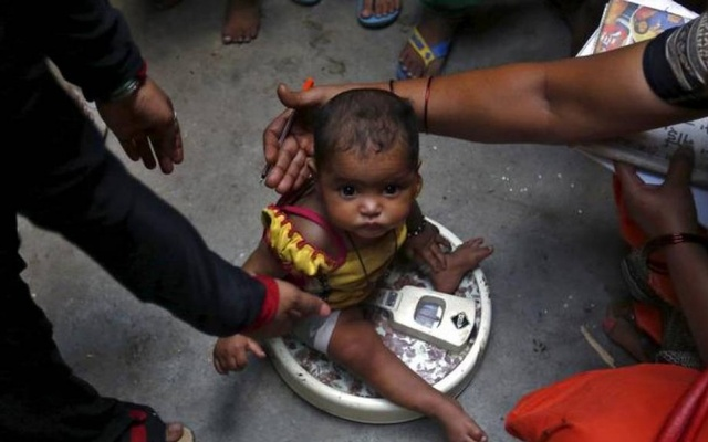 A health worker (R) weighs a child under a government program in New Delhi, India. Representational image. Credit: Reuters/Files