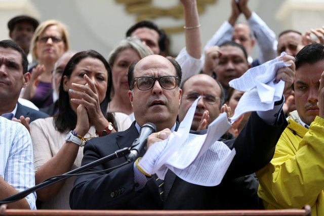 Julio Borges (C), President of the National Assembly and deputy of the Venezuelan coalition of opposition parties (MUD), tears a copy of a sentence of the Venezuela's Supreme Court during a news conference in Caracas, Venezuela March 30, 2017. Credit: Reuters
