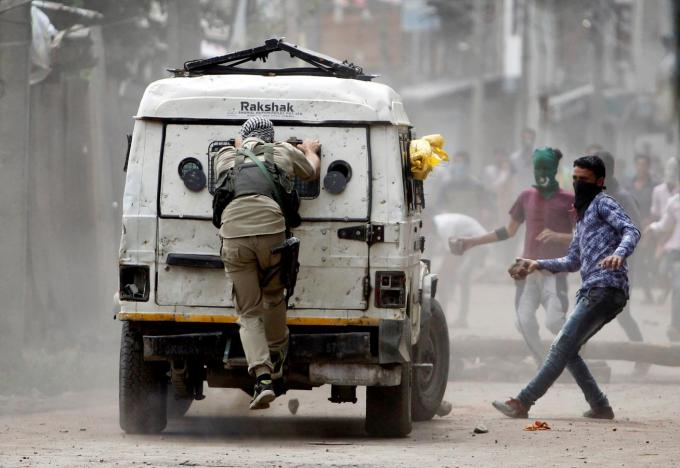 Demonstrators try to hurl stones at a police vehicle during a protest in Srinagar after Burhan Wani's killing and security force violence against protestors August 30, 2016. Credit: Reuters/Danish Ismail/File Photo
