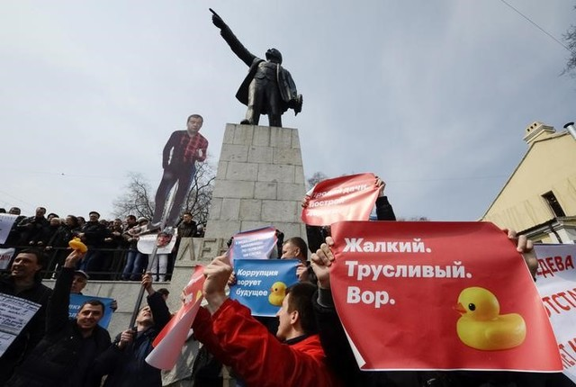 "Opposition supporters hold posters and a cutout figure depicting Prime Minister Dmitry Medvedev during a rally in front of a monument of Soviet state founder Vladimir Lenin in Vladivostok, Russia, March 26, 2017. Sign on right poster reads: ""Pathetic. Cowardly. Thief."" Credit: Reuters"